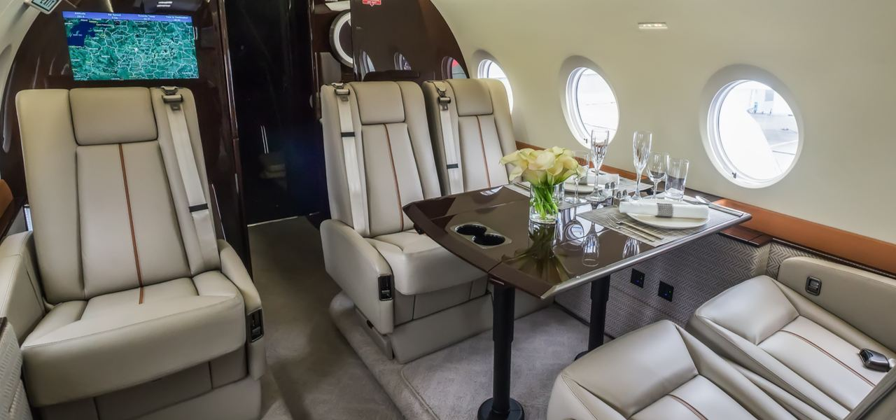 interior of luxury private jet with grey leather seats and table set for dinner