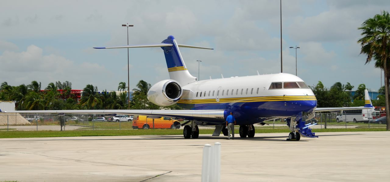 white blue and yellow Bombardier Global 5000 luxury jet on runway