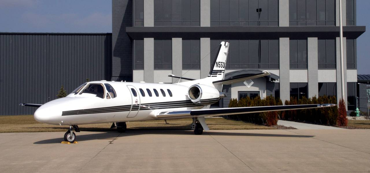 Luxury private jet parked in front of a building on a sunny day
