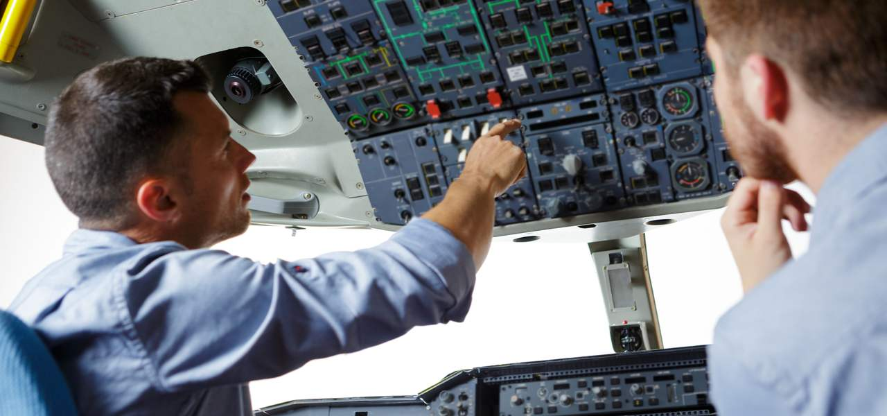Man showing pilot student aircraft navigation system while training