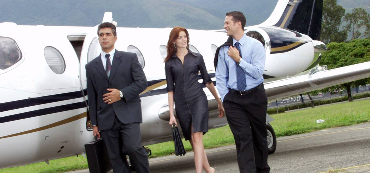 Two businessmen and a businesswoman walk disembark a private jet