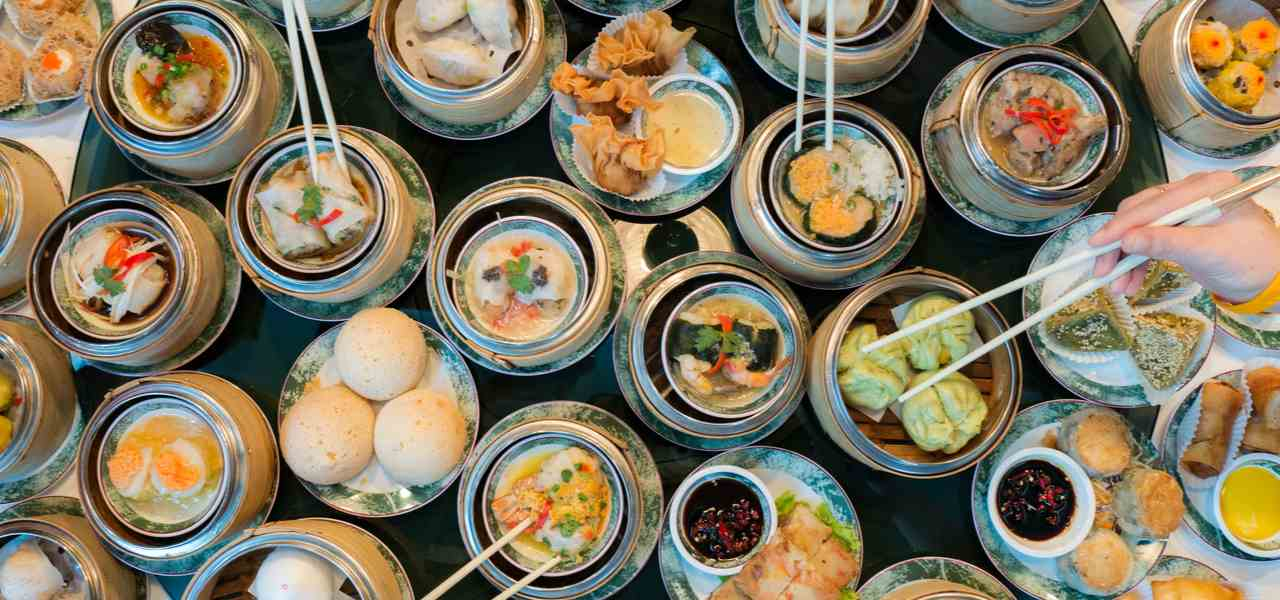 Overhead shot of many dim sum Chinese food dishes being shared