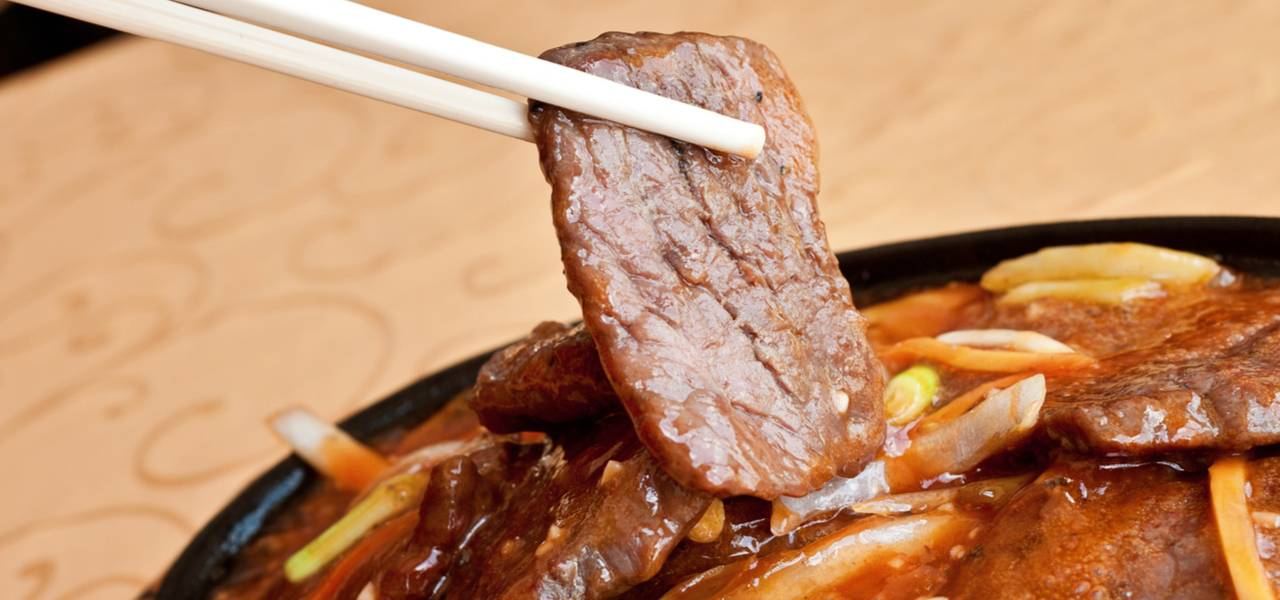 Close up of chopstick holding a juicy piece of Chinese beef