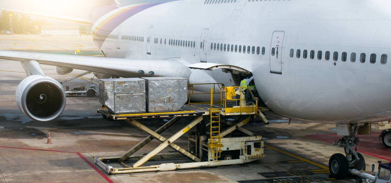 Cargo being loaded into airplane using forklift