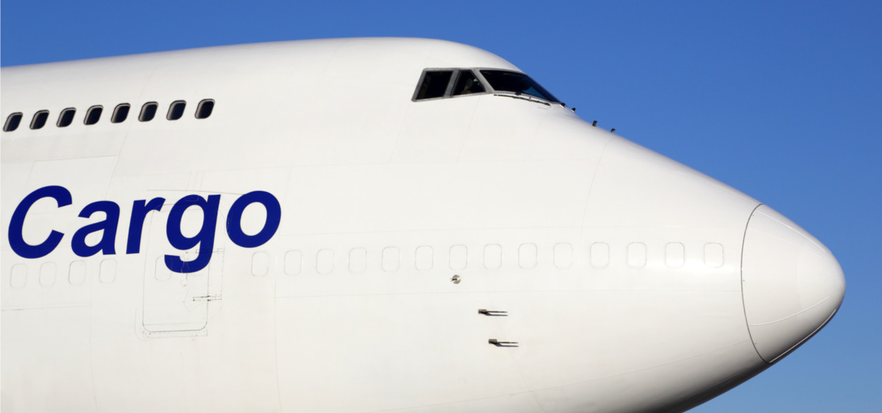 Front nose of large white cargo plane with the word cargo written on it in blue