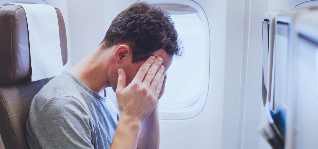 Man on airplane holding his temples