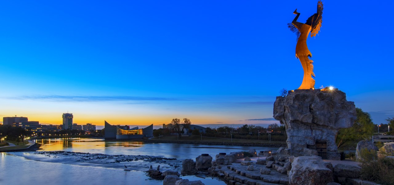 Giant Keeper of the Plains Statue in Wichita City with sun setting over the skyline of Wichita city in the background