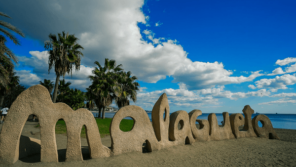 Sunny summer vacation scene in Malaga Spain with blue sky sea and sand