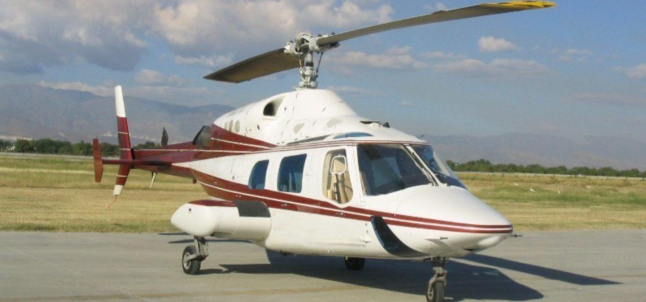 Бело-красный вертолет Bell 222 припаркован в аэропорту