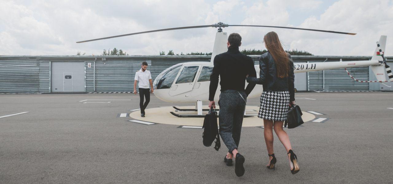 Молодая модная пара идет навстречу пилоту белого частного вертолета