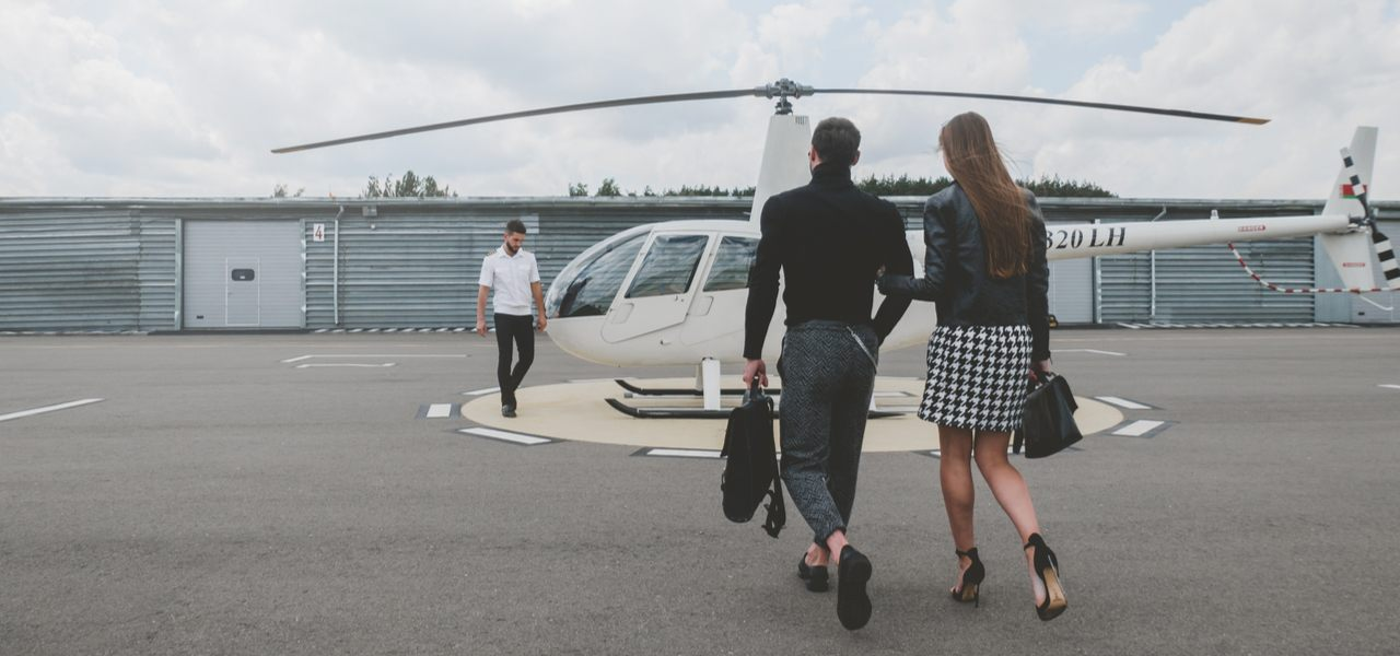 Young fashionable couple walk to meet pilot at white private helicopter