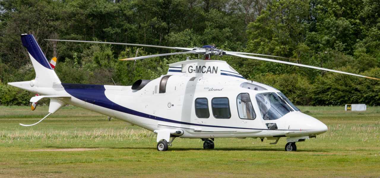 Бело-синий вертолет AW109 Power Grand на траве