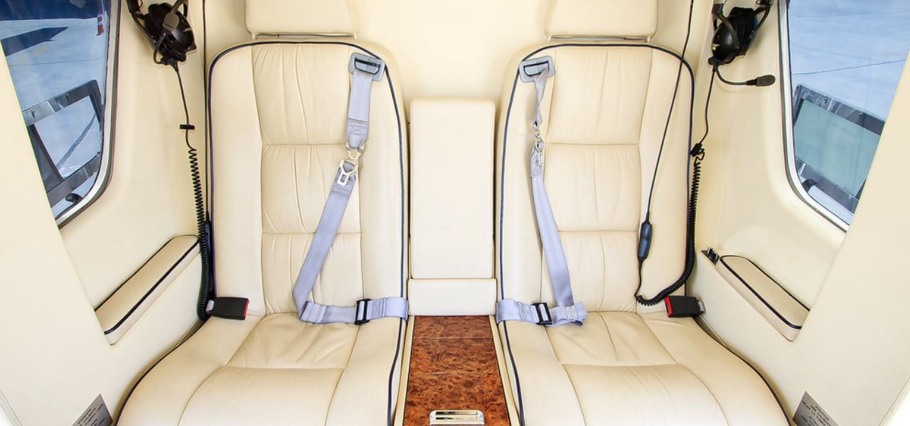 Interior of AS350 helicopter with two white leather seats