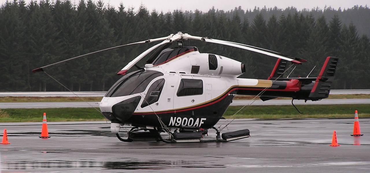 Вертолет MD900 на взлетно-посадочной полосе во влажных погодных условиях с деревьями на заднем фоне