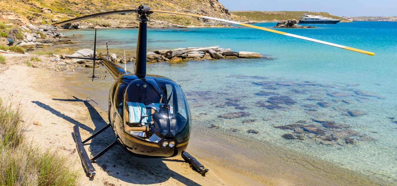Robinson R22 helicopter parked on a beach