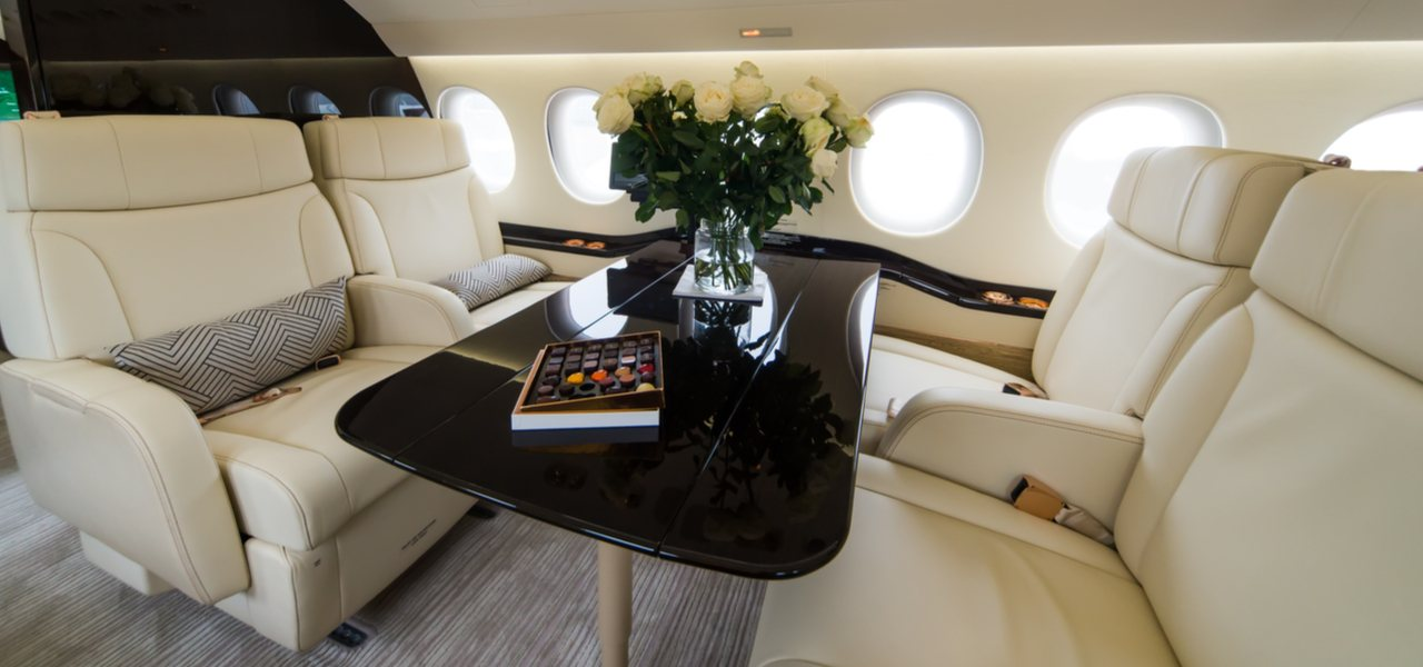 White leather interior of luxury jet with roses on table