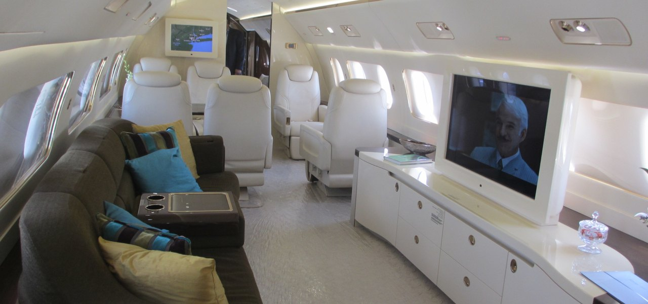 Embraer Lineage 1000E interior with white leather seats and brown sofa