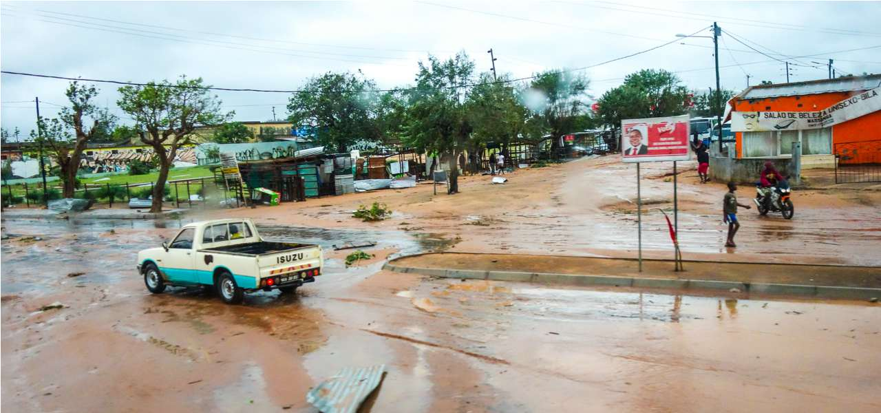 A car makes its way down a waterlogged street during floods in Maputo, Mozambique in 2013