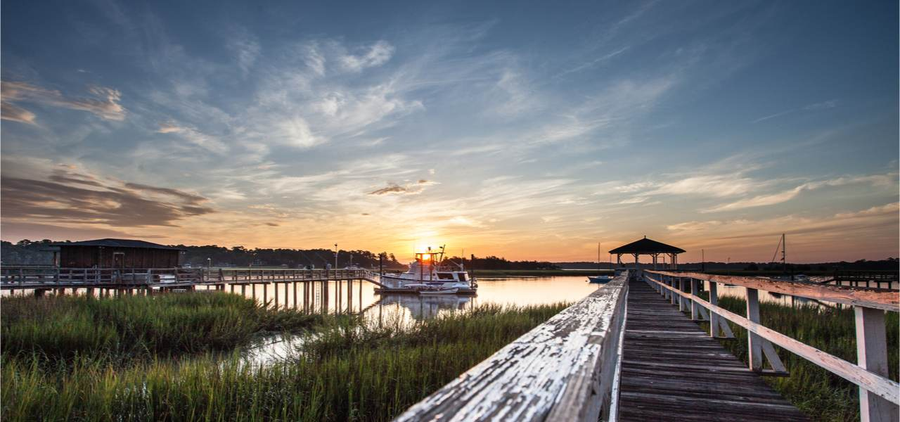 Old wooden dock leading to a beautiful sunrise over the marsh in Savannah