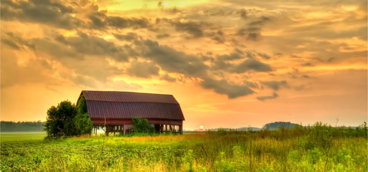 Sunset over a farm field with a traditional red barn at the horizon