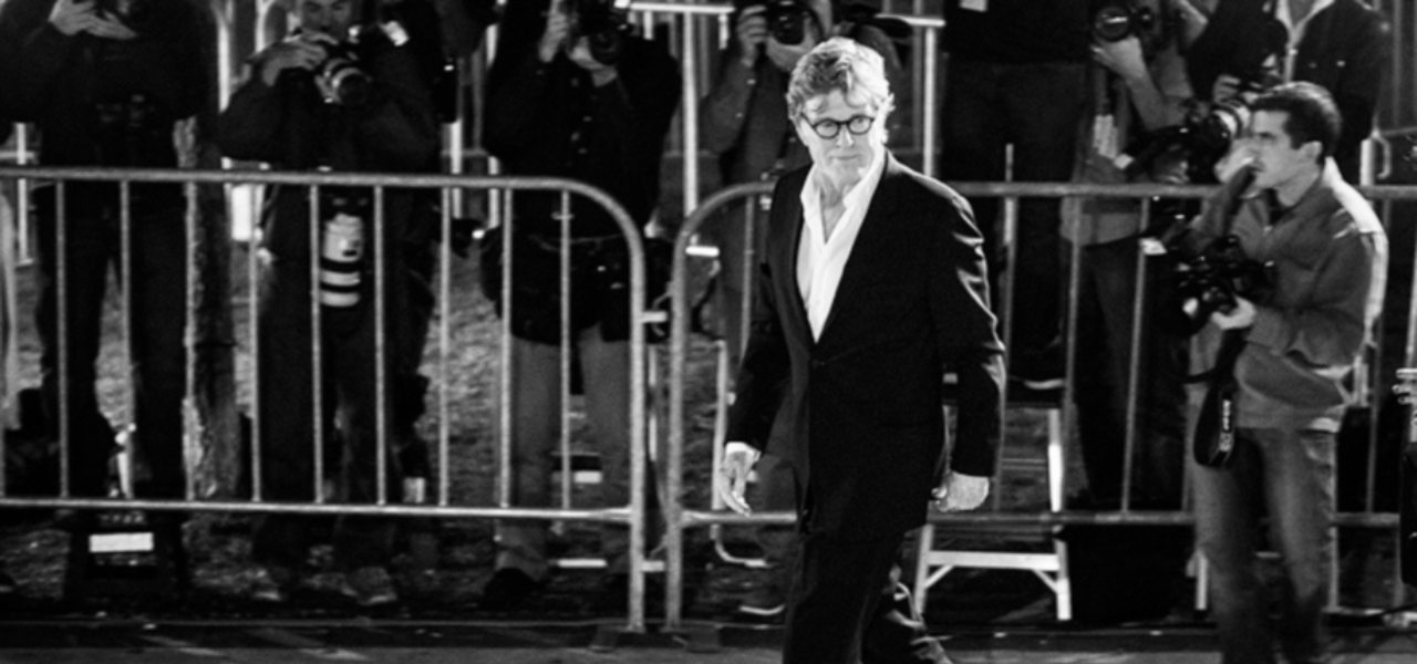 Black and white image of movie actor Robert Redford wearing glasses and a suit being photographed at an event