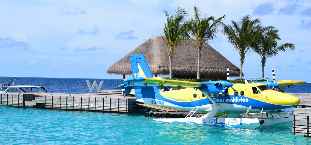 Yellow, blue and white seaplane docked on the ocean by the palm trees of a Maldives holiday hut.