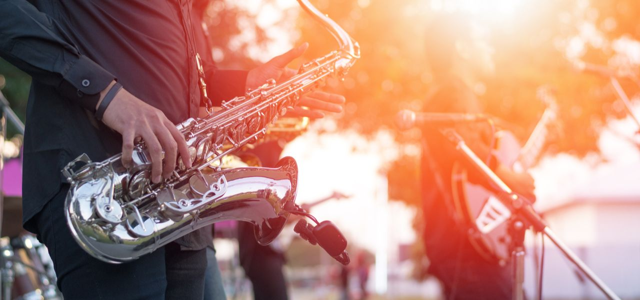 Close up of saxophone being played by a member of a jazz group at sunset
