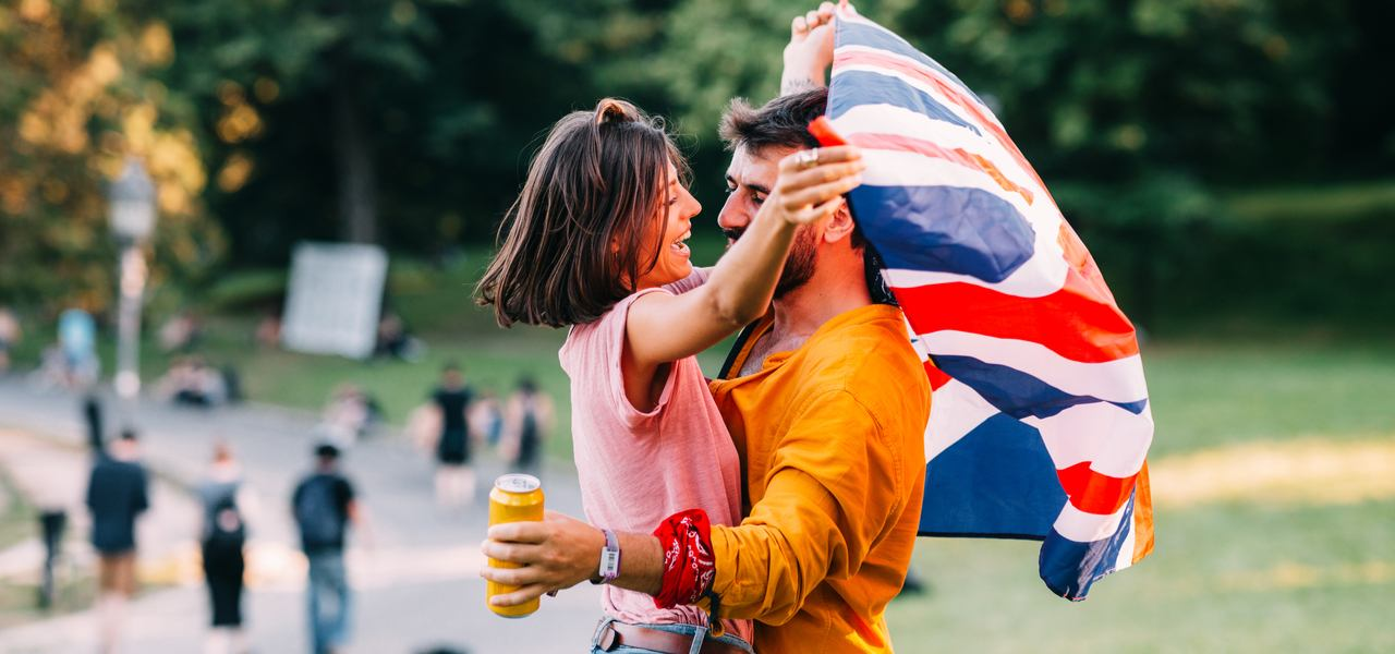 Happy couple embracing at a music festival with UK flag