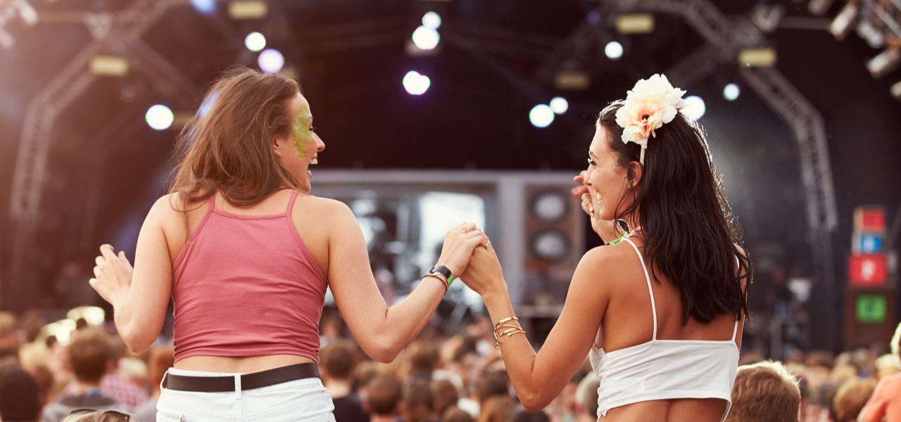 Two girls on shoulders holding hands at a music festival