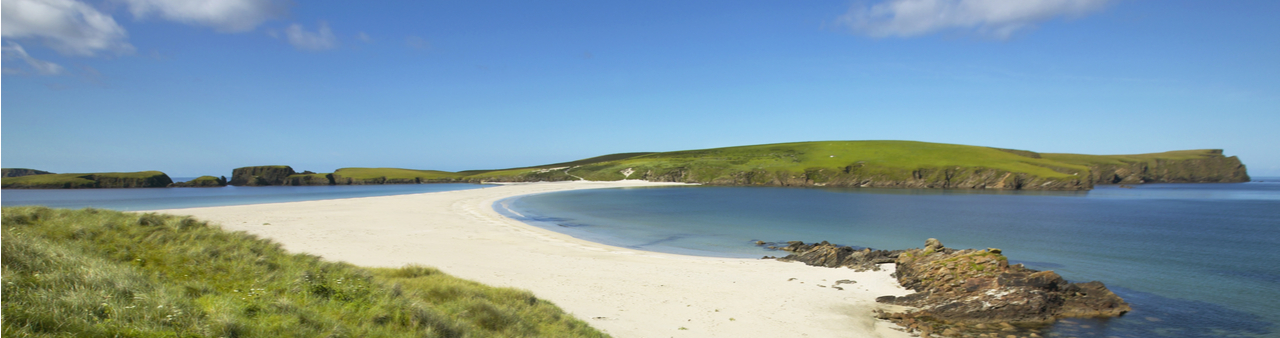 Marram grass, pale sand and calm sea under a blue morning sky at a remote destination on the Shetland Islands