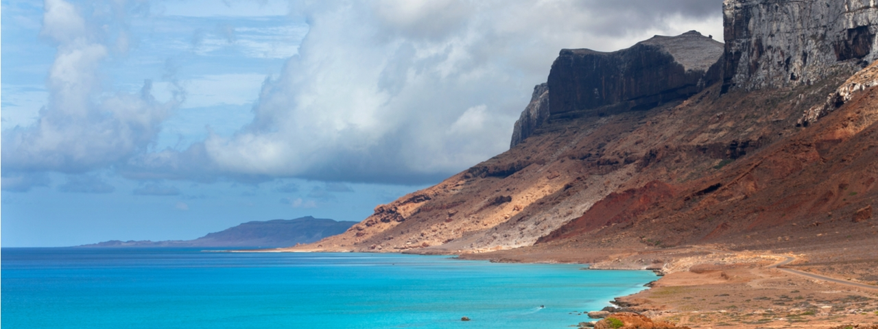 The beach in Socotra with pink rock and grey cliffs over the turquoise Arabian Sea