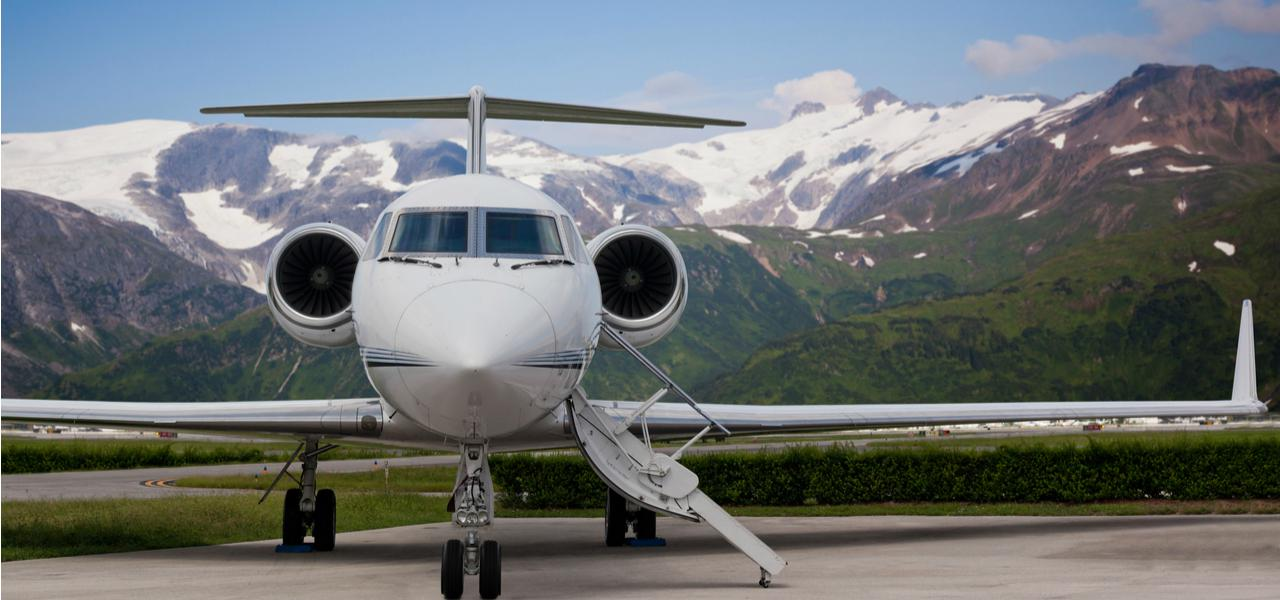 Luxury private jet ready for boarding with snow peak mountains in the background