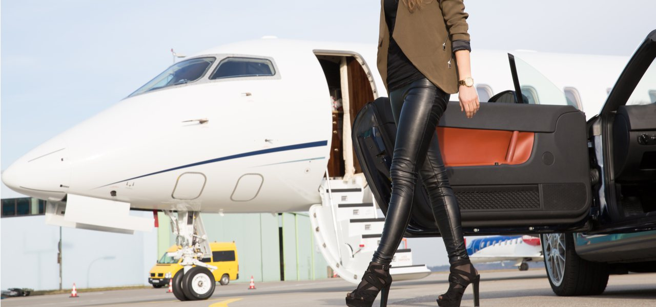 A fashionable woman getting out of her car in front of a private jet