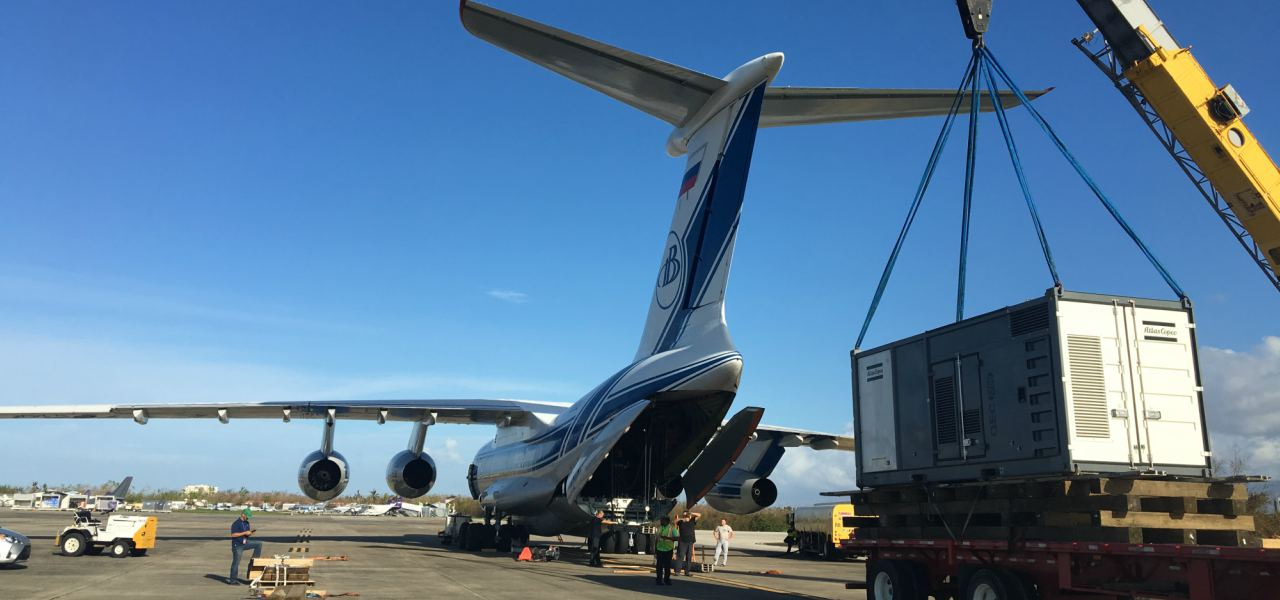 A flatbed truck on a runway gets ready to load an electrical transformer onto an Ilyushin-76, bound for Puerto Rico