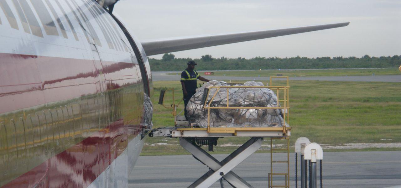 A man loads humanitarian aid packages into an Antonov-12 bound for Haiti