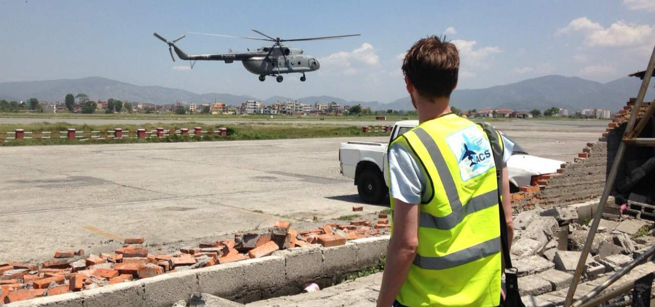 A man wearing an ACS vest looks on as a helicopter leaves an airfield with humanitarian aid for victims of the Nepalese earthquake in 2015