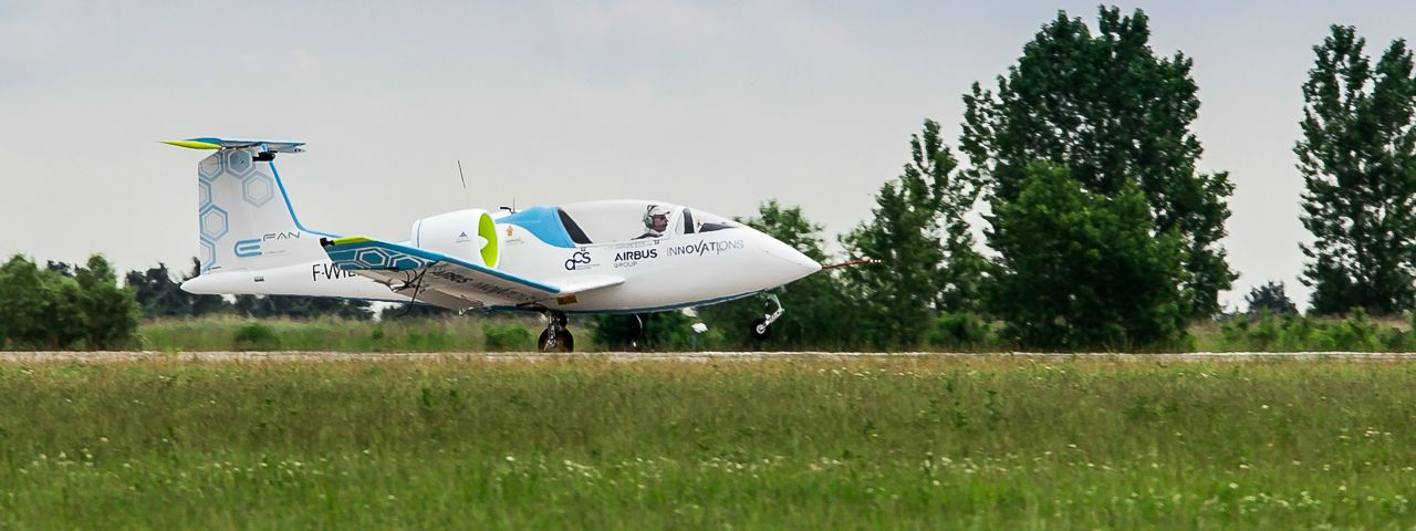 An Airbus E-Fan taking off from a small runway surrounded by countryside