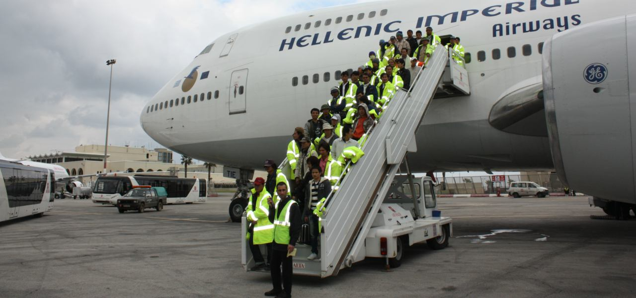 Airline personnel stand on a stairway leading up to a passenger jet