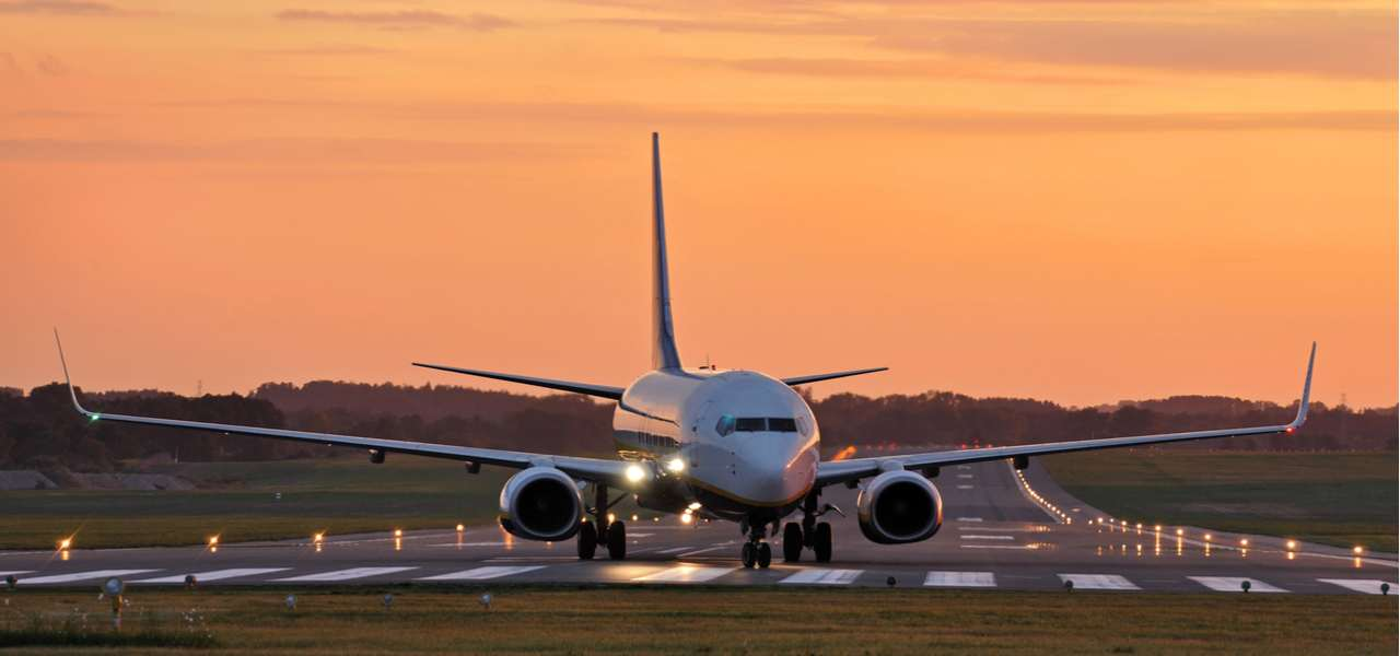 An airliner lands on the tarmac at sunset