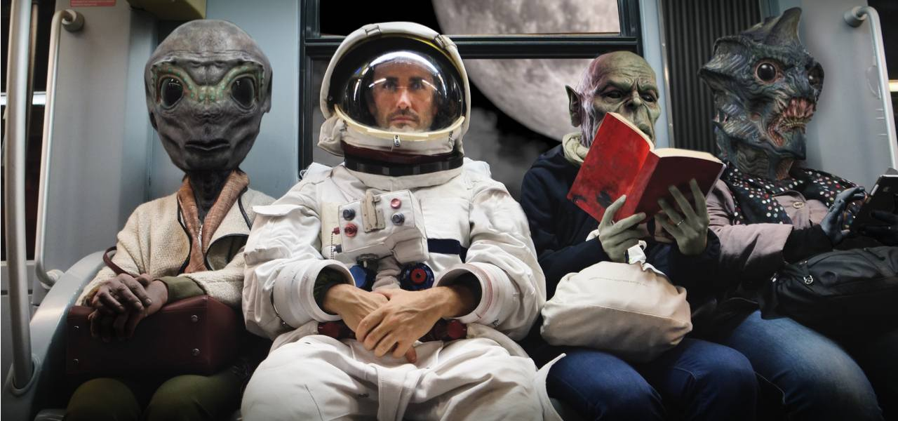 An astronaut in a space-suit sits alongside three alien passengers on board a spaceship