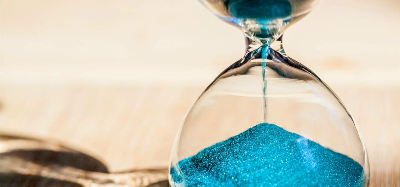 Blue Sand running through the bulbs of an hourglass measuring the passing time