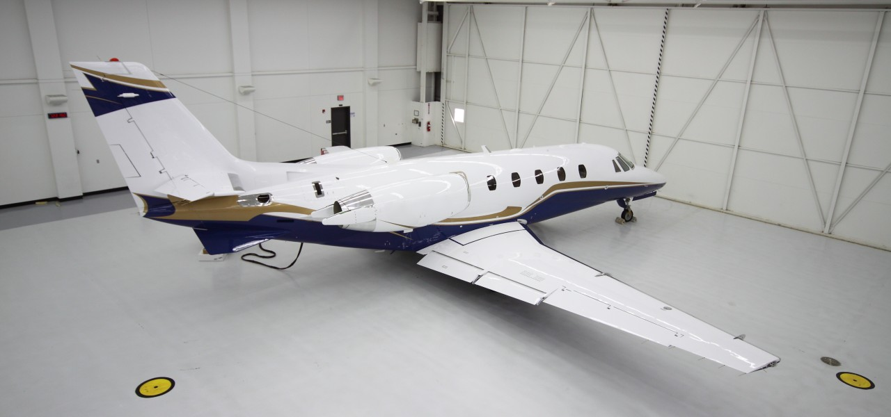 Brand new blue and white private jet in a brand new hangar