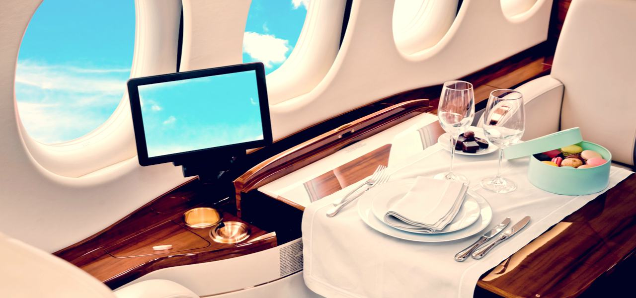 Business Jet airplane interior with luxury wooden table and blue sky outside window