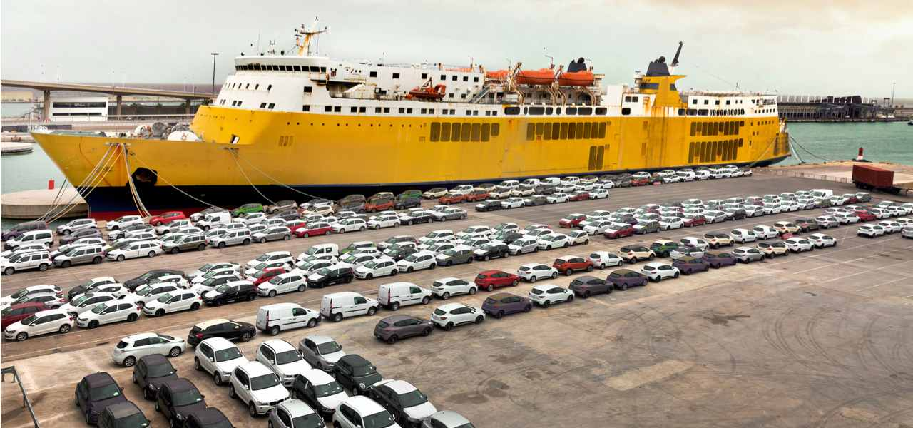 Cars line up in front of a cargo freighter preparing to load in a harbour