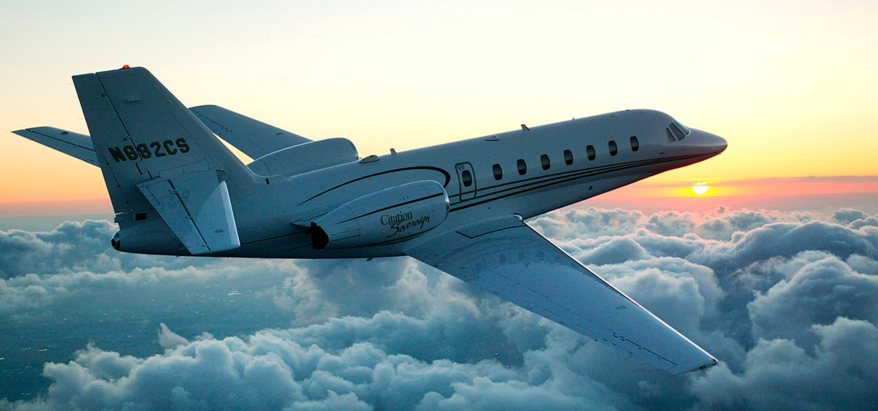 A Cessna Citation Sovereign+ flying with clouds underneath.