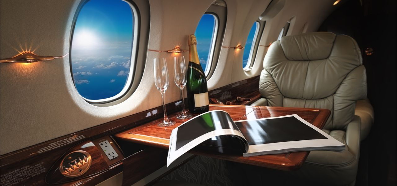 Interior of a modern and luxurious business jet with two glasses and a bottle of champagne on the table
