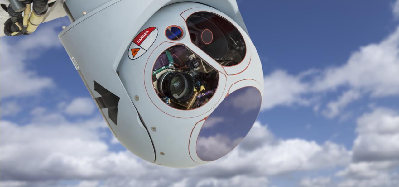 Futuristic closeup of drone camera sensor pod module in blue sky with clouds