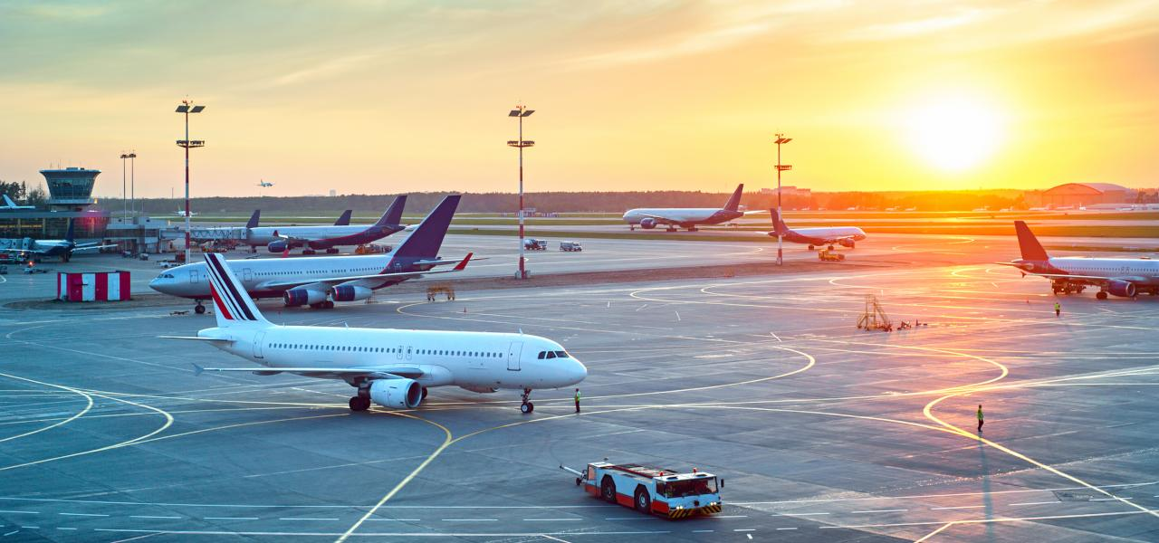 A range of commercial airliners stationed at an airport with the sun setting in the distance