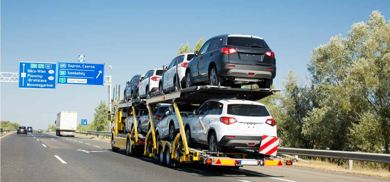 A delivery truck transports a load of cars along a highway