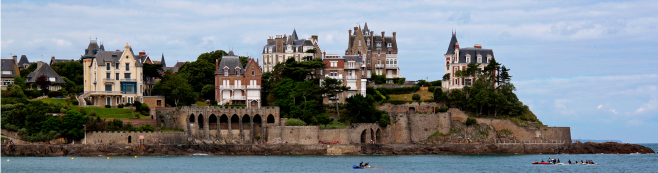 The idyllic French coastal town of Dinard with billionaires' vacation homes above the sea, canoes below, and a blue cloudy sky above